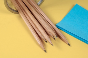 Pencils and Blue Postit Notes on a Yellow Background